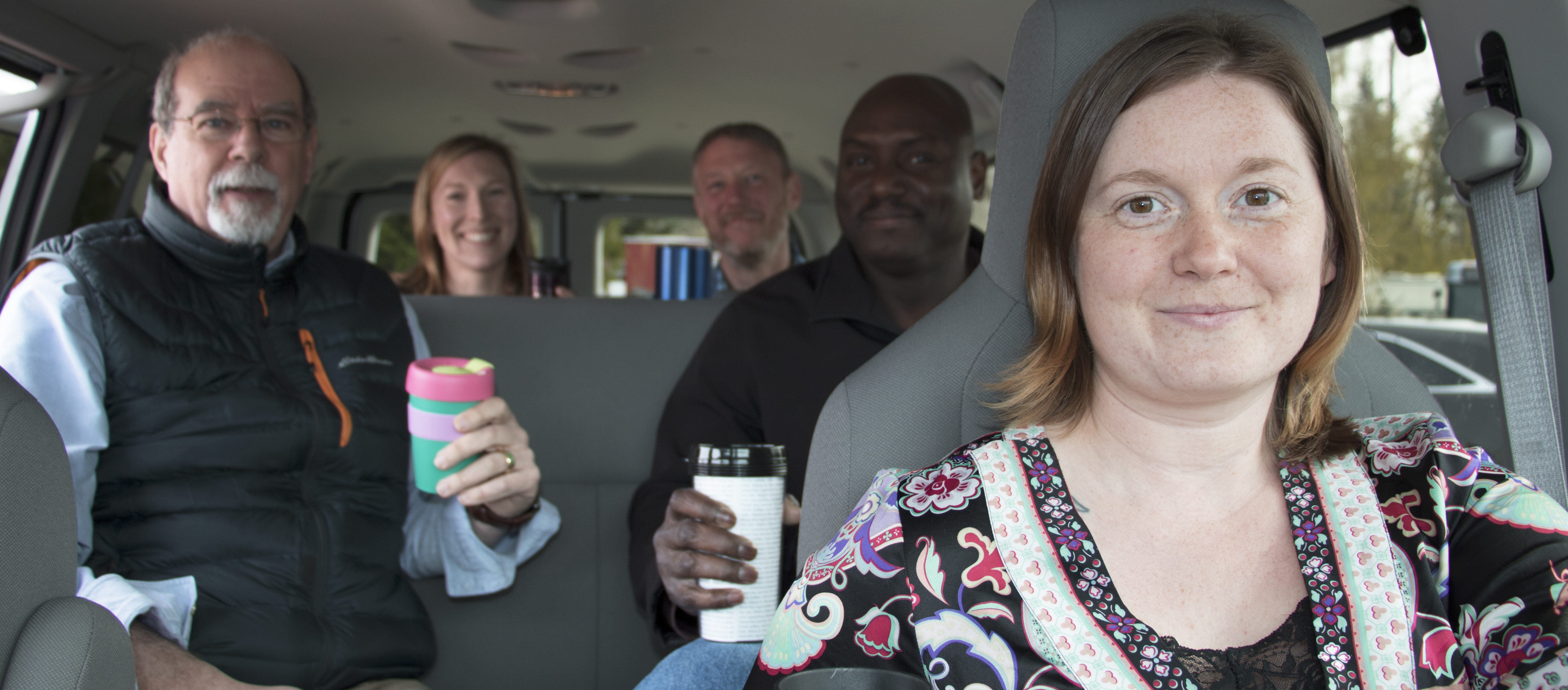 Five people with coffee in a vanpool