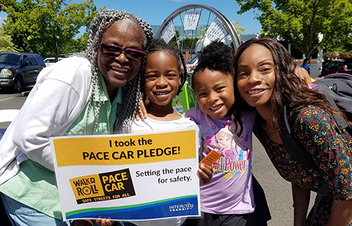 Image of family holding Pace Car Pledge sign