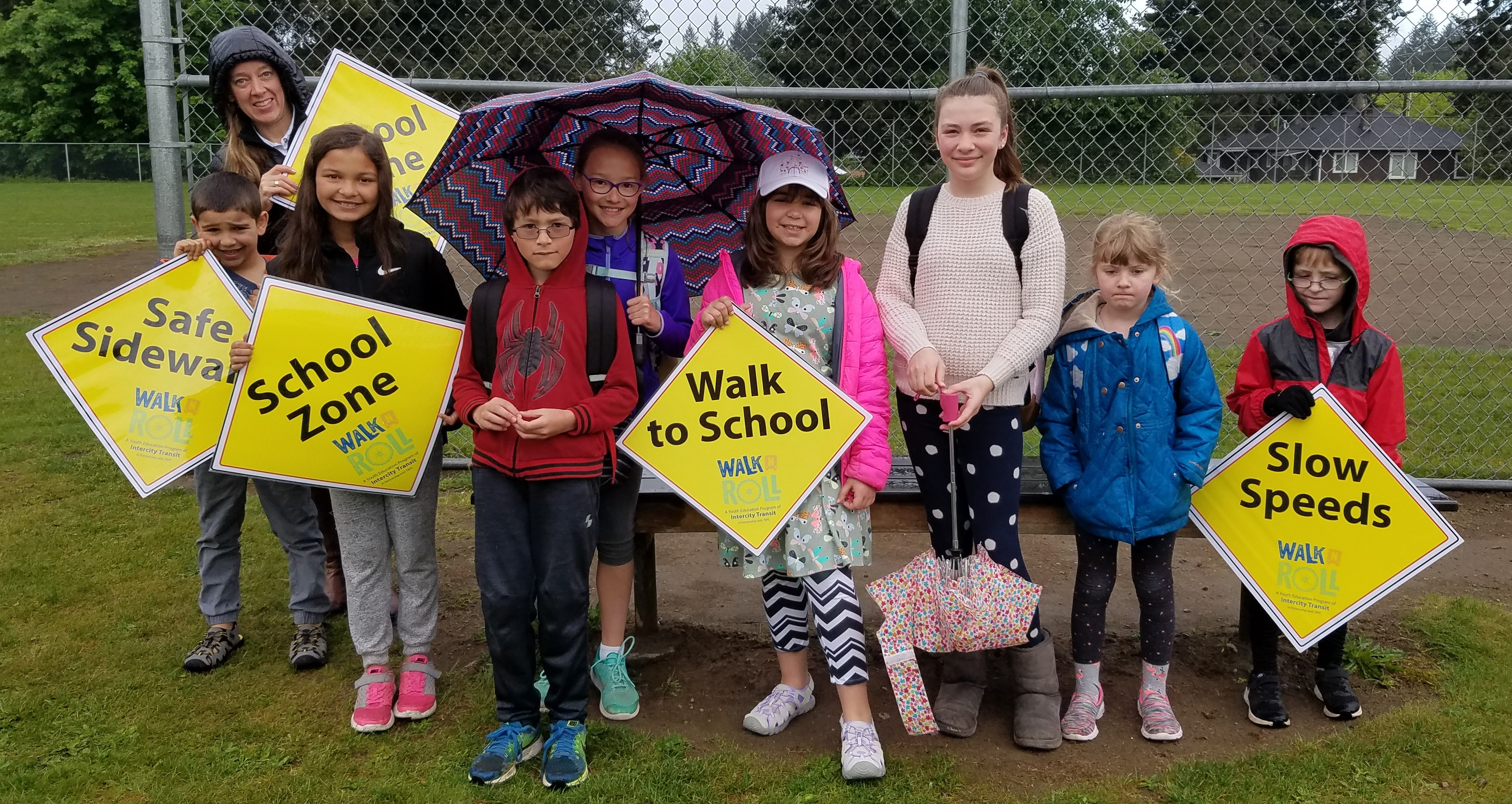 Kids and teacher at school holding Walk N Roll signs