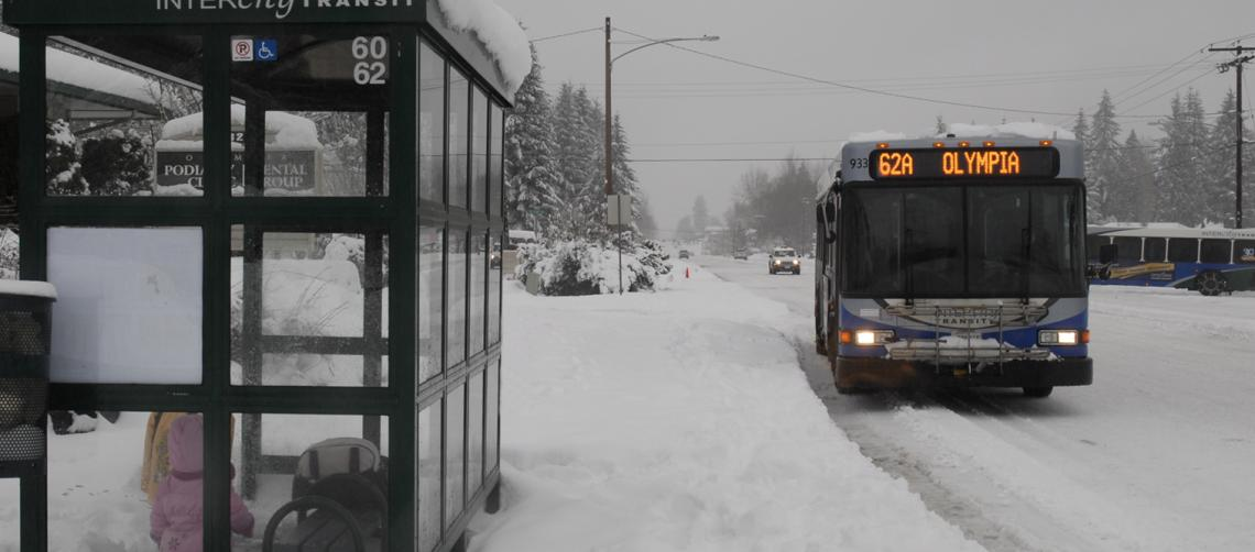 A bus in the snow stopping for passengers