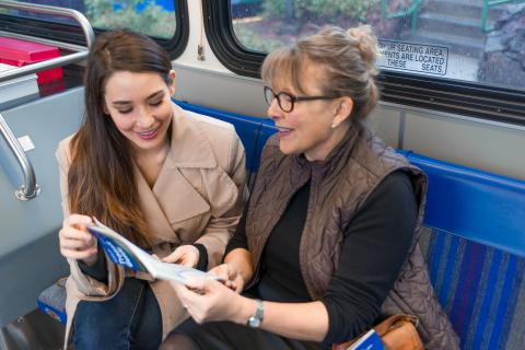 A travel trainer and passenger talking on a bus