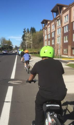Kids riding bicycles in bike lane on street